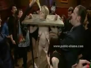Blonde dress teared down while she is immobilized in cows device in the middle of public