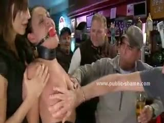 Brunette whore is put on display for people in a bar while being tied up and gagged